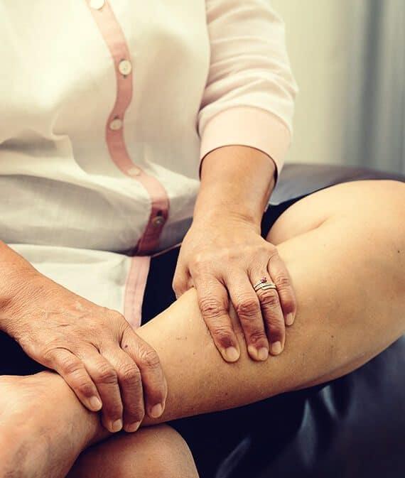 woman rubbing sore leg