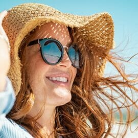 A woman smiling on the beach with sunglasses and a sunhat.
