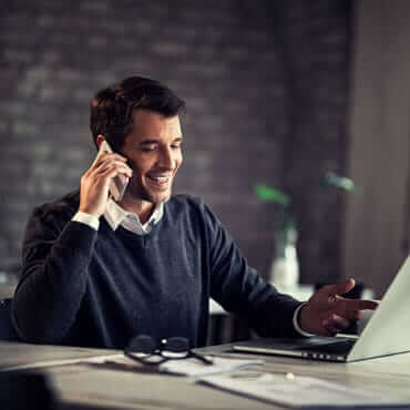 affiliate conducting business on the phone and at a laptop