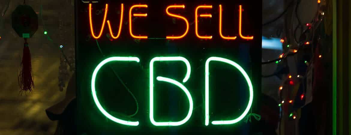 """Neon store sign reading """"We Sell"""" in orange and """"CBD"""" in green."""