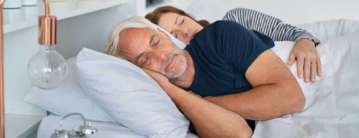 older couple sleeping in a bed