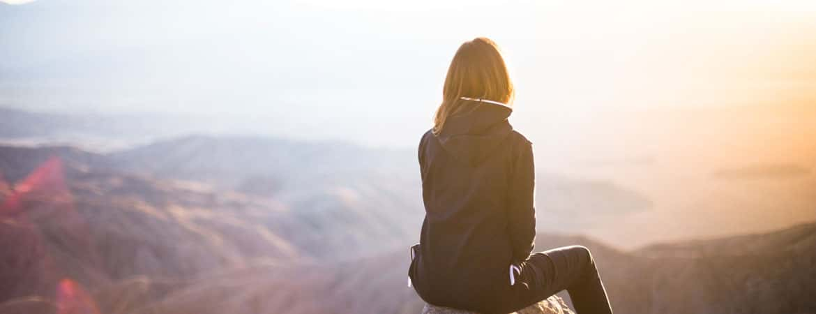 woman looking out over a beautiful mountain range