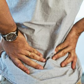 A middle aged man holding the arch of his back in pain.