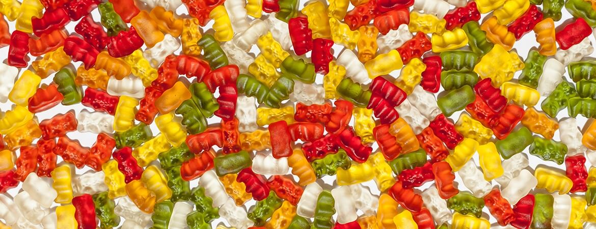 A colorful array of CBD gummies placed into a single layer on a table.