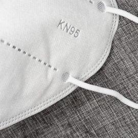 A KN95 mask sitting on grey carpet.